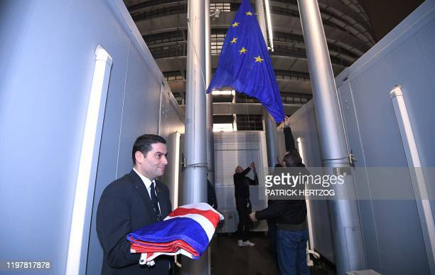 Staff members remove the United Kingdom's flag from the European Parliament, in Strasbourg, on January 31 on Brexit Day. - Britain leaves the...