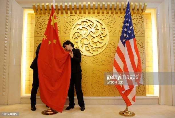 Staff members set up Chinese and US flags for a meeting between Chinese Transport Minister Li Xiaopeng and US Secretary of Transportation Elaine Chao...