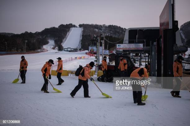 Staff members shovel snow at at the foot of a slope of the Yongpyong ski resort near the venues of the Pyeongchang Winter Olympic games, in...