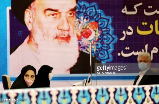 Staff members sit under a portrait of the Islamic republic's late revolutionary leader Ayatollah Ruhollah Khomeini, while registering candidates for...