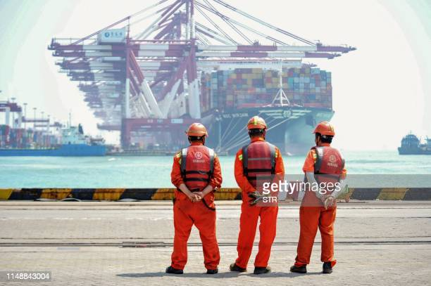 Staff members stand at a port in Qingdao in China's eastern Shandong province on June 10 2019 China's exports beat gloomy forecasts to rebound in May...