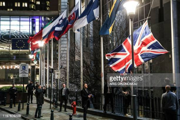 TOPSHOT Staff members take down the United Kingdom's flag from outside the European Parliament building in Brussels on Brexit Day January 31 2020...