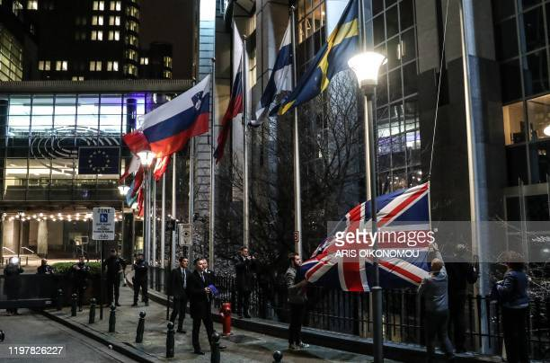 Staff members take down the United Kingdom's flag from outside the European Parliament building in Brussels on Brexit Day January 31 2020 Britain...