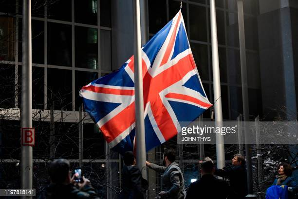 Staff members take down the United Kingdom's flag from the European Parliament building in Brussels on Brexit Day January 31 2020 Britain leaves the...