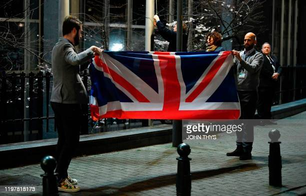 TOPSHOT Staff members take down the United Kingdom's flag from the European Parliament building in Brussels on Brexit Day January 31 2020 Britain...