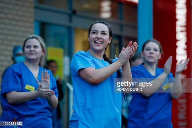 """Staff members take part in a national """"clap for carers"""" to show thanks for the work of Britain's National Health Service workers and frontline..."""