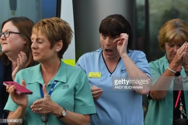 NHS staff members take part in a national clap for carers to show thanks for the work of Britain's National Health Service workers and frontline...