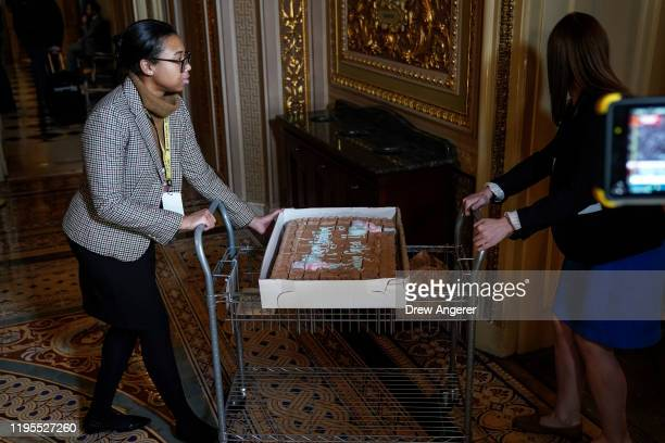 Staff members transport a birthday cake for Sen Tom Carper into the Senate Cloakroom during the impeachment trial of President Donald Trump at the US...