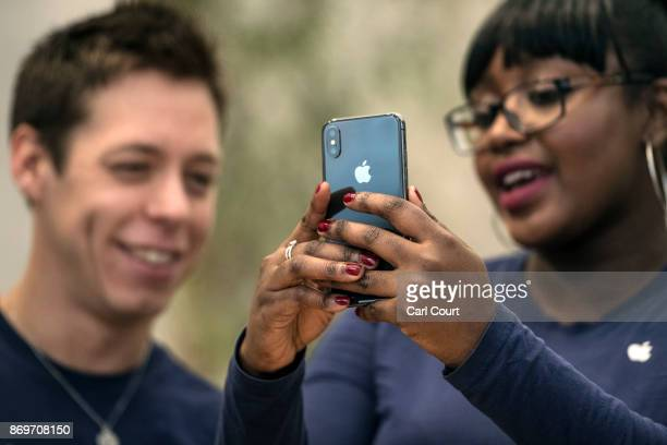 Staff members view the new iPhone X in the Apple store upon its release in the UK on November 3 2017 in London England The iPhone X is positioned as...