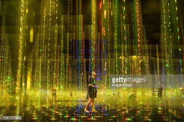 """Staff members walk inside an interactive installation """"Ephemeral Solidified Light"""" during a media preview of the """"teamLab Reconnect: Art with Rinkan..."""