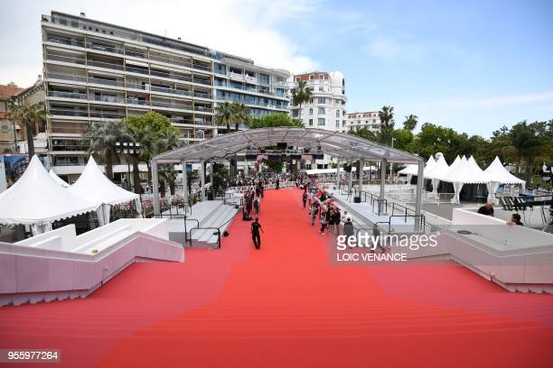 Staff members walk on the red carpet outside the festival's palace on May 8 2018 ahead of the opening of the 71st edition of the Cannes Film Festival...