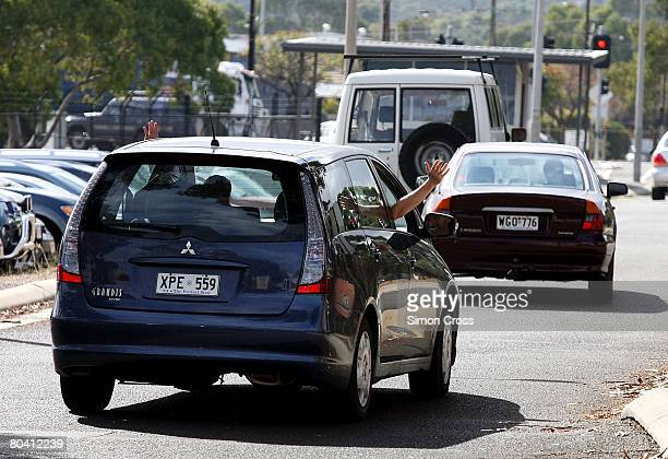 Staff members wave out of their cars as they leave the Tonsley Park Mitsubishi manufacturing plant for the last time on March 28 2008 in Adelaide...
