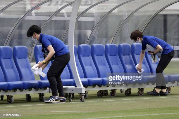 Staff members wearing protective face masks wipe and sanitize a team bench prior to an operational test match for the Rugby Sevens event of the...