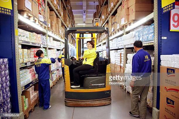 Staff members work at a Metro AG supermarket in Shanghai China on Wednesday May 19 2010 Metro AG Germany's largest retailer plans to add 100 stores...