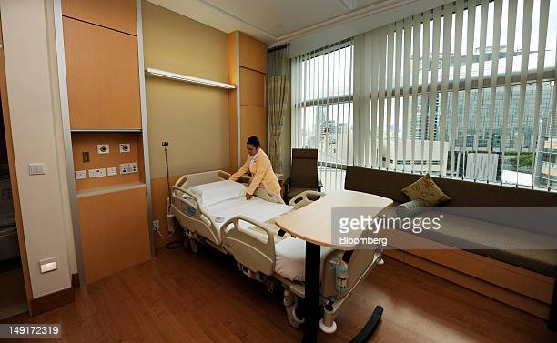 Staff nurse Rhoda Jaclyn adjusts the bedding in the Premiere suite of IHH Healthcare Bhd's Mount Elizabeth Novena Hospital in Singapore on Monday...