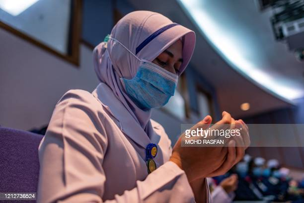 A staff nurse wearing a face mask as a preventive measure against the spread of the COVID19 novel coronavirus offers prayers during a ceremony to...