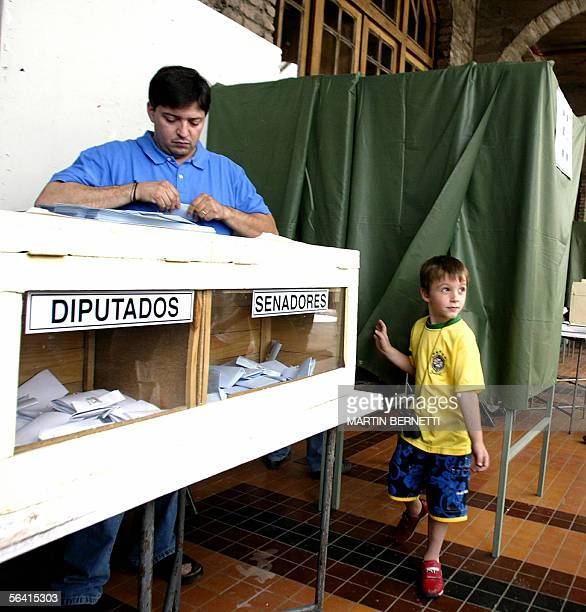 A staff of a polling station accomodates ballots on top of ballot boxes for deputies and senators as a boy plays around a polling booth in Santiago...