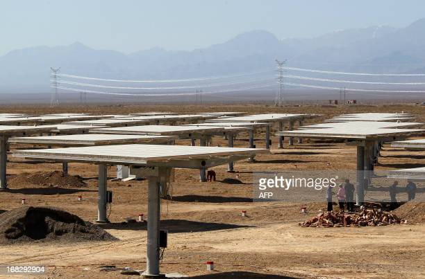 Staff of a solar power plant works on their solar panels in Hami northwest China's Xinjiang Uygur Autonomous Region on May 8 2013 The EU executive on...