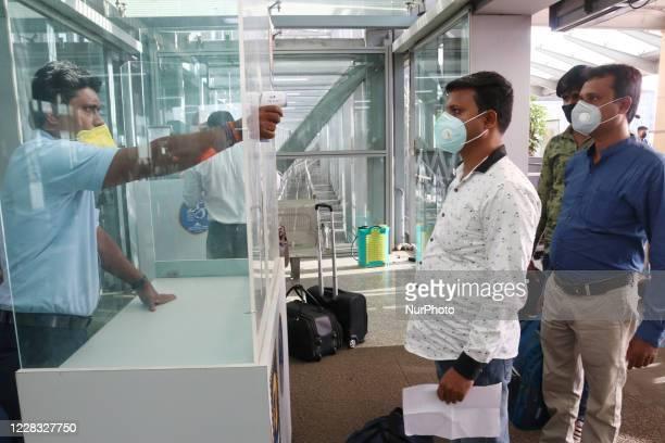 Staff of Airport Screening temperature a Passenger at Netaji Subhash Chandra Bose International Airport in Kolkata on September 03,2020.Government...