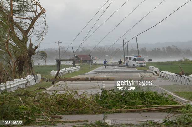 TOPSHOT Staff of an ambulance carrying a sick child try to clear a road of debris and toppled electric posts caused by strong winds from super...