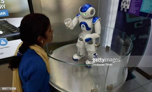 A staff of Canara Bank demonstrates Candi the robot which welcomes customers as receptionists at Bengaluru Circle Office on September 21 2017 in...