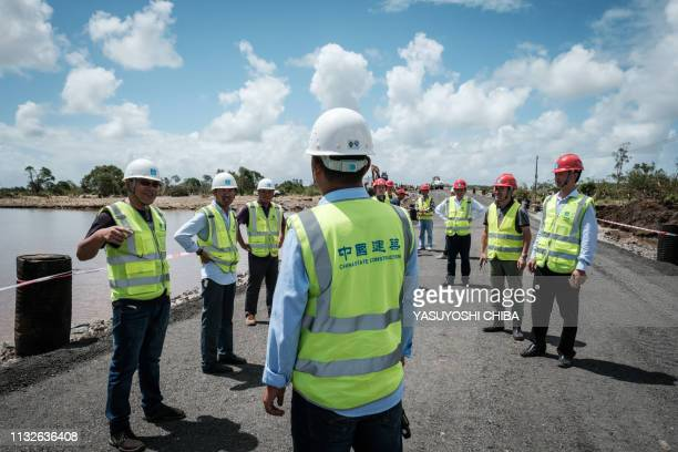 Staff of China State Construction wait for the opening of the N6 national road rebuilt in three days after the original road was destroyed by the...