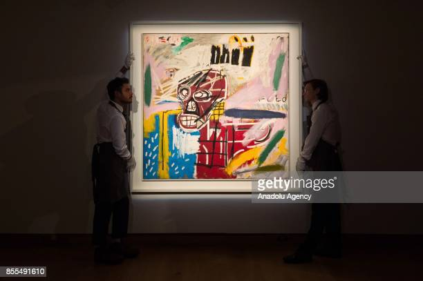 Staff of Christie carry an artwork titled Red Skull created by artist JeanMichel Basquiat during the Christie's Frieze Week Auction Highlights in...