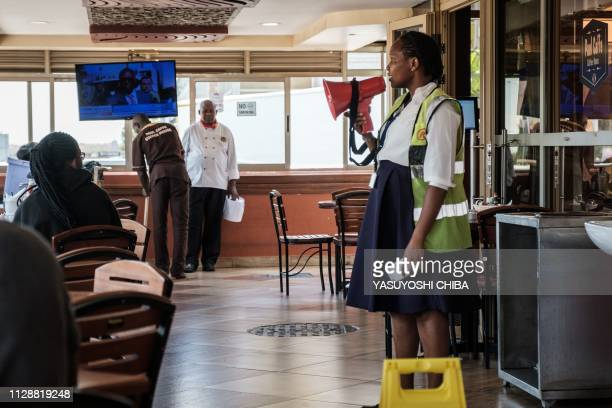 A staff of Kenya Airways uses a megaphone to speka to waiting passengers at a restaurant next to the departure terminal due to a strike by airline...