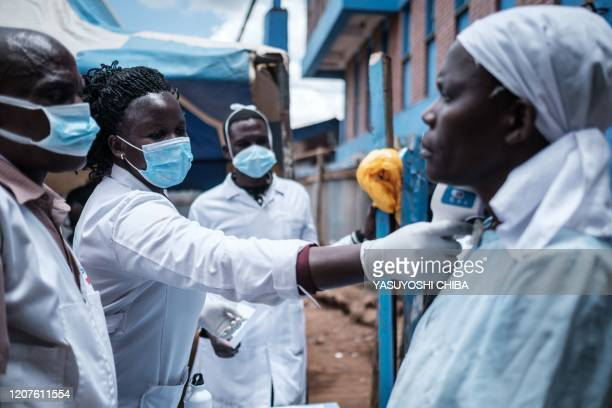 Staff of local NGO Shining Hope for Communities measures a woman's body tempreture as the NGO installs hand washing stations at the Kibera slum in...