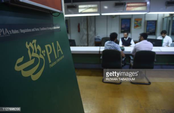 Staff of Pakistan International Airlines talk with passengers at a PIA office in Karachi on February 27 2019 Numerous flights were cancelled or...