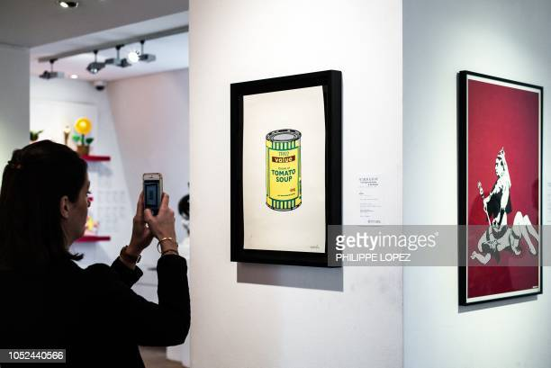A staff of the Artcurial French auction house takes pictures of artworks by street artist Banksy prior to an Artcurial sale at in Paris on October 18...