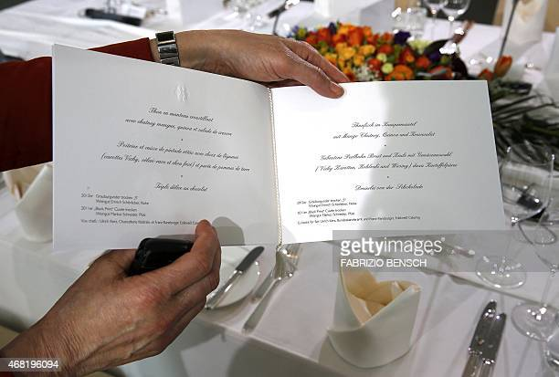 A staff of the Chancellery shows the menu card of the working lunch between the delegations of German Chancellor Angela Merkel and French President...