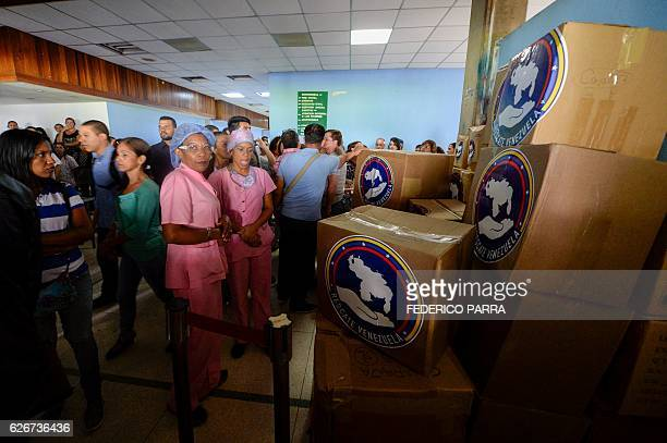 Staff of the Dr Jose Gregorio Hernandez Hospital stand next to boxes with donations delivered by opposition members at Catia neighbourhood in Caracas...