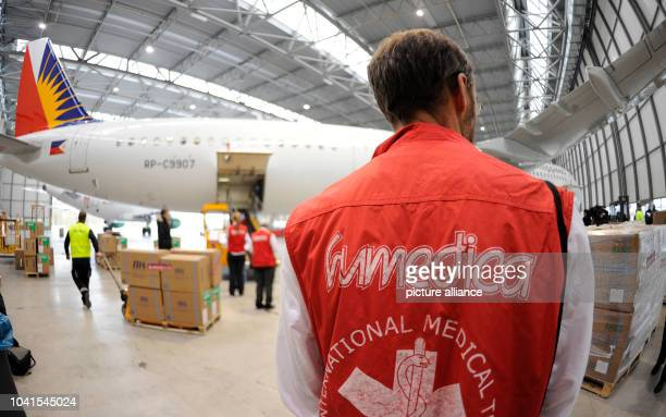 Staff of the Humedica Medical Team overlooks the loading of an A321 Airbus aircraft with relief supplies the disaster region in the Philippines at...