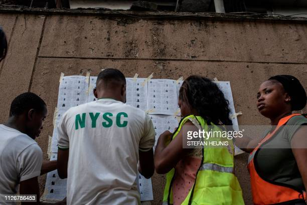 TOPSHOT Staff of the Independent National Electoral Commission attach voter registers to a wall at one of the polling stations in Lagos on February...