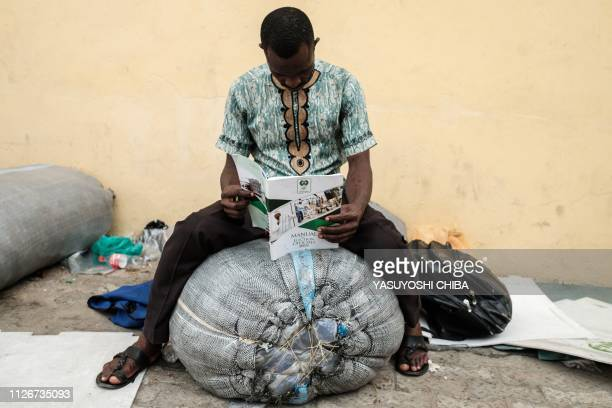 TOPSHOT A staff of the Independent National Electoral Commission sits and reads the manual for election officials during the electoral preparation at...