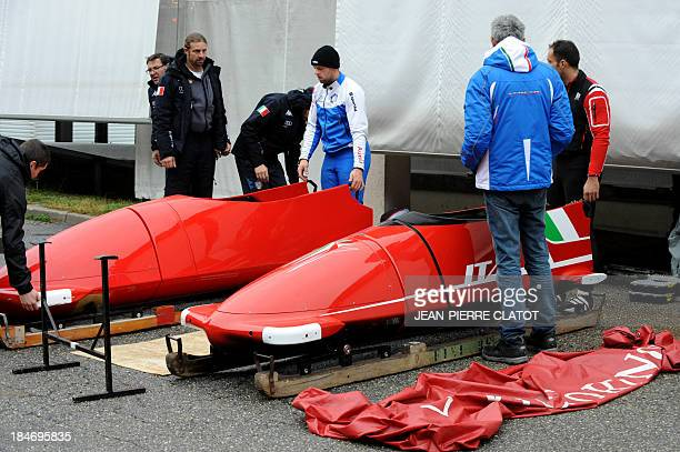 Staff of the Italian bobsleigh team prepare on October 15 2013 bobsleighs designed and engineered by Italian carmaker Ferrari before training in the...