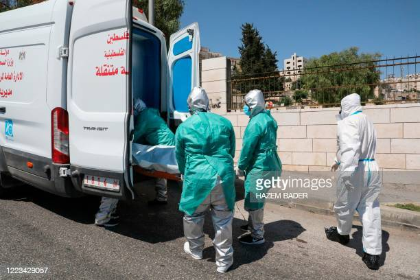 Staff of the Palestinian Ministry of Health in protective suits transport the body of 47yearold Palestinian COVID19 victim Nassra Abu Hussein for...