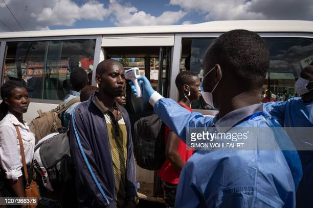 Staff of the Rwanda Biomedical Center screens passengers at a bus station after the government suspended all unnecessary movements for two weeks to...