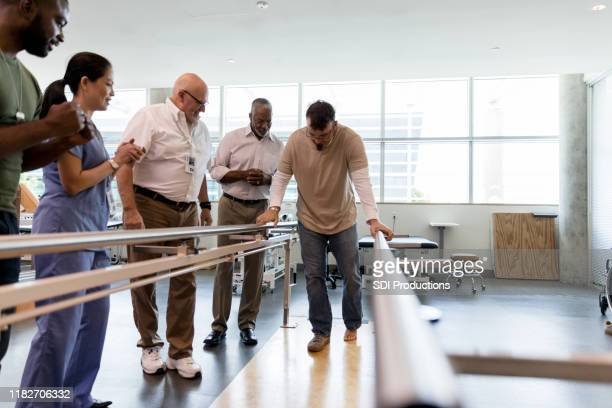 staff of the therapy clinic encourage patient's first steps - outpatient care stock pictures, royalty-free photos & images