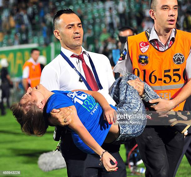 A staff of the Turkish Spor Toto Super League carries a fainted woman during the Turkish Spor Toto Super League match between Bursaspor and Besiktas...
