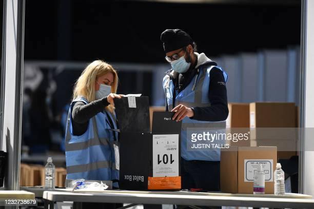 Staff open a ballot box to count for the local elections at the count centre at Olympia London in west London on May 7, 2021.
