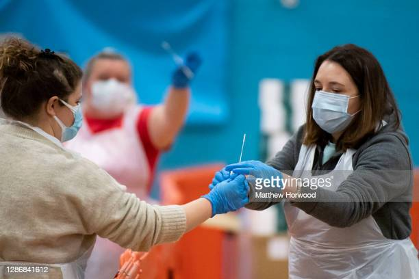 Staff pass a medical swab for analysis following a coronavirus test at Merthyr Tydfil Leisure Centre on November 21, 2020 in Merthyr Tydfil, Wales....