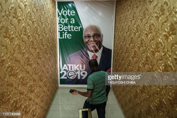 A staff passes in front of the poster of the Presidential candidate Atiku Abubakar of Nigeria's main opposition Peoples Democratic Party at PDP's...