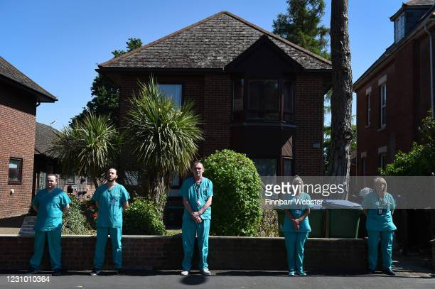 Staff pay their respects as the funeral cortege passes the entrance of the Southampton General Hospital on May 29 2020 in Southampton England...