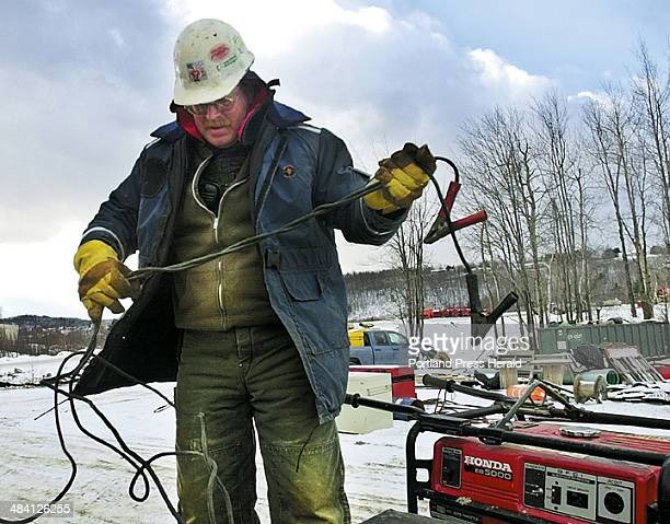 Staff photo / ANDY MOLLOY Paul Haley unfurls a pair of jumper cables before charging a diesel truck at the new bridge construction project in Augusta...