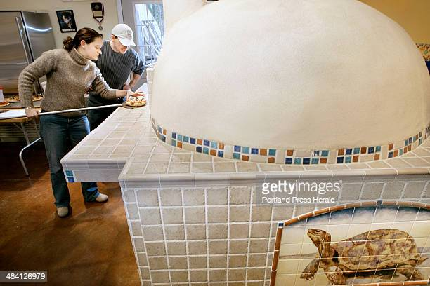 TJ McCann and Christine Jamoil of Dover NH remove a pizza from the woodfired panyol oven at Stone Turtle Baking and Cooking School in Lyman Jan 14...