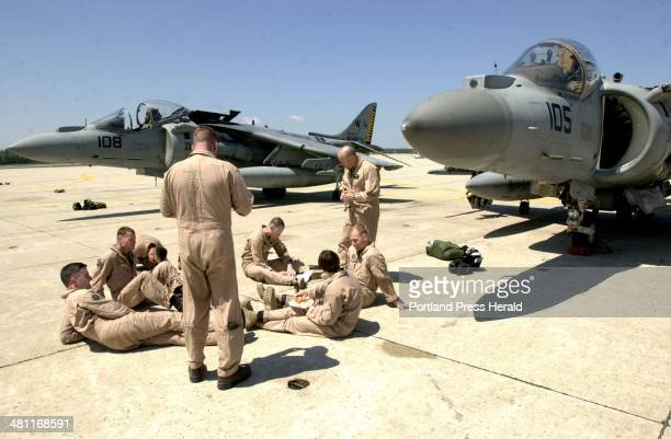 Staff Photo by Doug Jones Friday May 16 2003 After 8 hours in the air Harrier jet pilots lounged on the concrete runway next to their jets with a...
