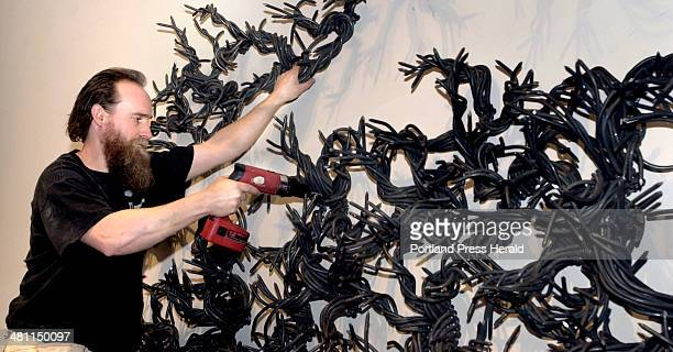 Staff Photo by Doug Jones, Wednesday, April 2, 2003: Sculptor John Bisbee in the process of attaching a ton of 12 inch spikes to the wall of the...