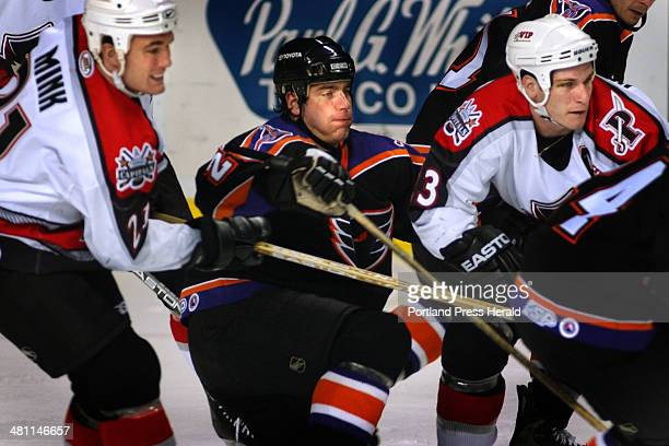 Staff Photo by Fred J. Field, Tue, Dec 31, 2002: Portland Pirates Graham Mink, 21 and Trent Whitfield take Philadelphia Phantom Brad Tiley, 28 out of...